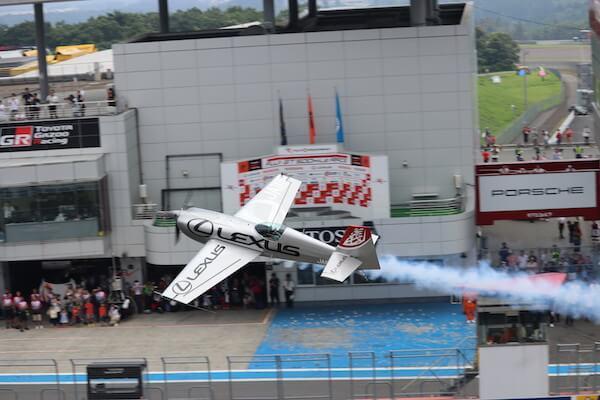富士スピードウェイのグランドスタンドを横切る航空機の写真